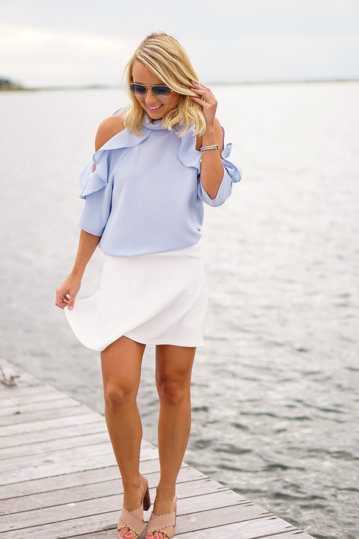 Blue ruffle Nordstrom top and Bauble Bar earrings and white skater skirt