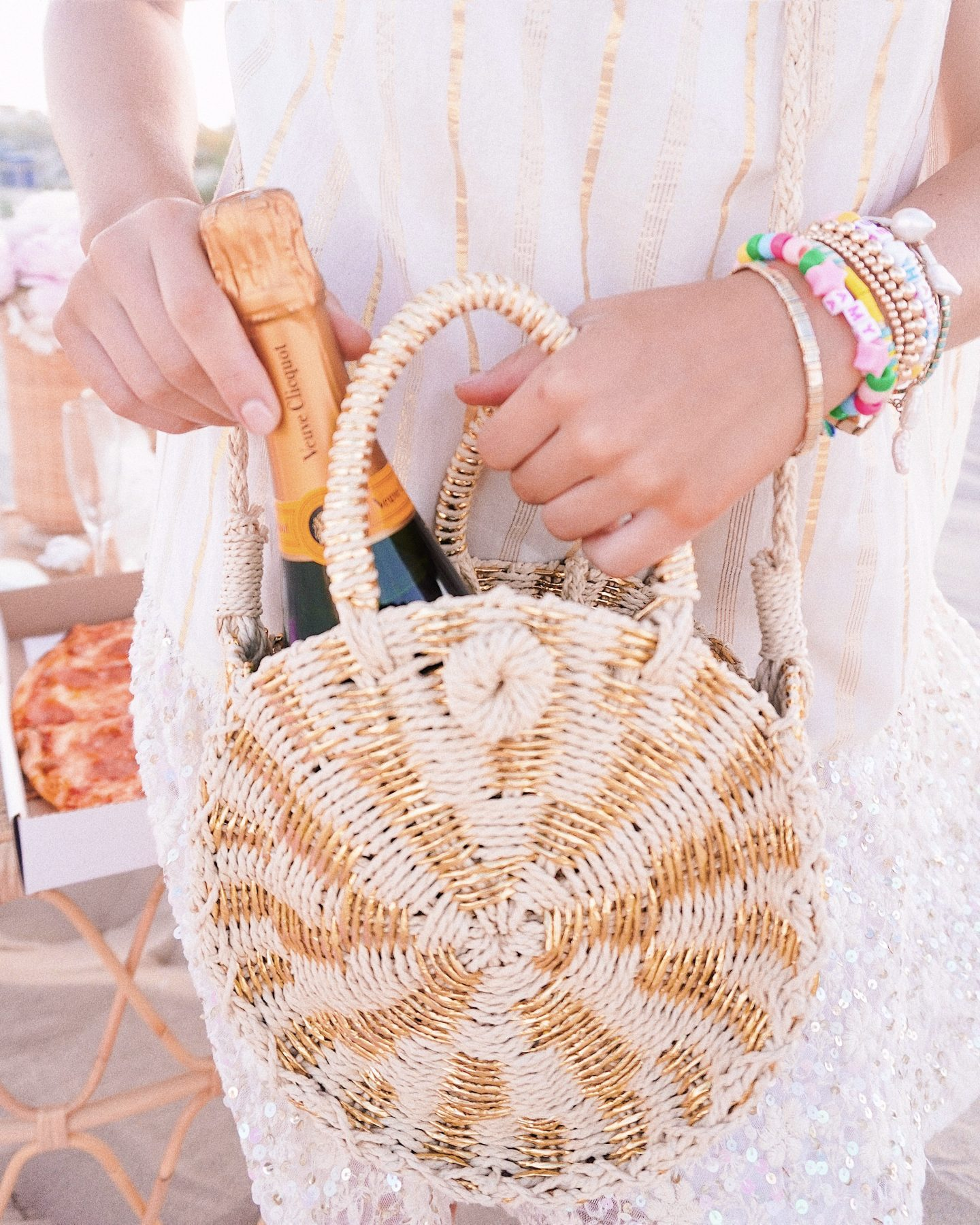 Gold straw bag and colorful beaded bracelets